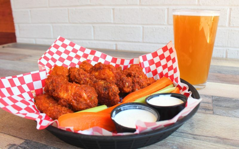 Chicken wings on a plate next to a glass of beer.